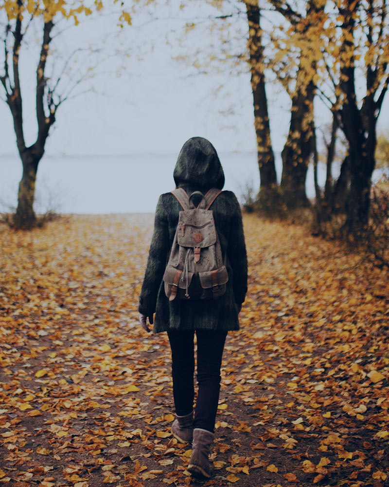 Woman walking through autumn leaves