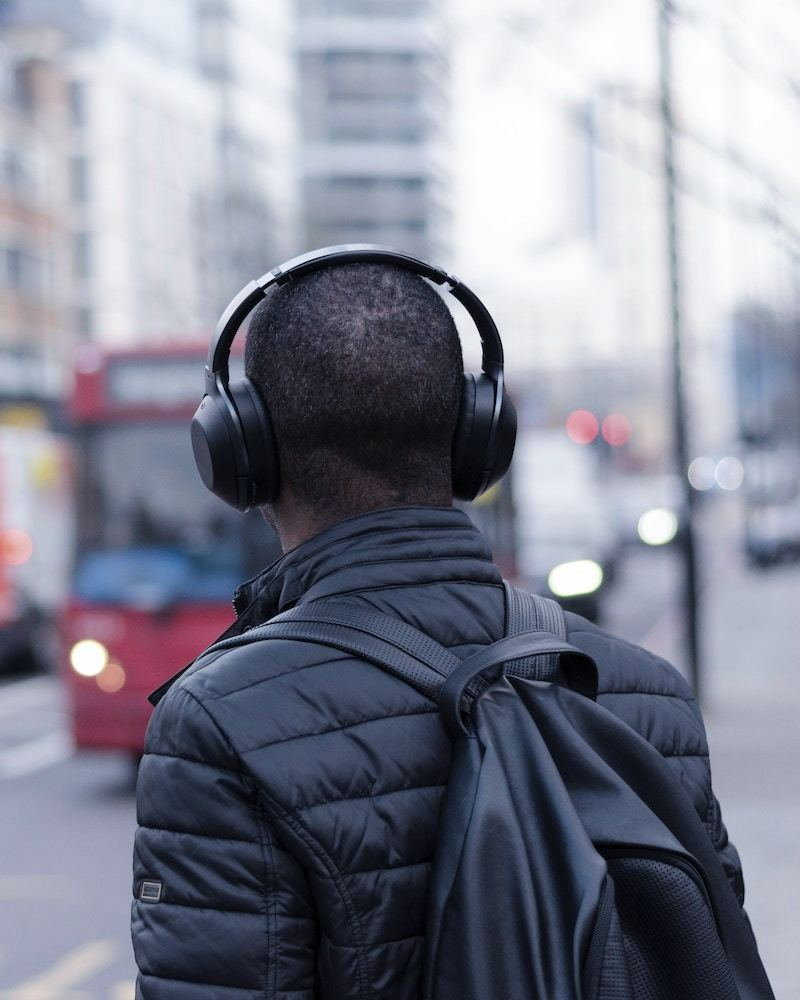 Man waiting for London bus with headphones on